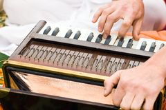 Hands of man playing mantra on accordion. Hands of man playing Krishna mantra on accordion royalty free stock image