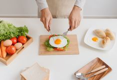Hands of man prepare breakfast with sandwich with poached eggs.  Royalty Free Stock Photography