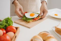 Hands of man prepare breakfast with sandwich with poached eggs.  Royalty Free Stock Images