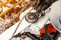 Hands a man puts on a chainsaw on the tooth wheel of an electric saw. Woodcutter mechanics, equipment. Hands a man puts on a chainsaw on tooth wheel of an stock photos