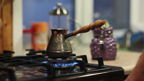 Hands of a man putting a coffee pot on a cooker, setting fire. Hands of a man putting a metal coffee pot with along handle on a cooker, setting fire stock video