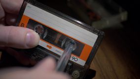 Hands of a man rewinding a compact cassette. With the help of a pen stock video footage