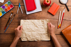 Hands of man with rumpled paper. Various school supplies. Royalty Free Stock Photo
