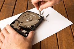Hands of a man with a screwdriver disassembling the hard drive stock image