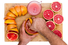 Hands of a man squeezing fresh ruby grapefruit Royalty Free Stock Photos