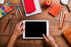 Hands of man with tablet. Various school supplies. Royalty Free Stock Image