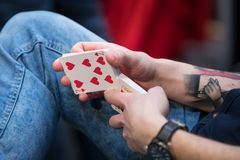 Hands of a man with a tattoo shuffles a deck of cards royalty free stock image