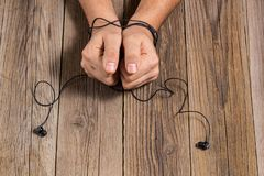 hands of man tied with phone headset, as the concept of man& x27;s dependence on music, technology Royalty Free Stock Photography
