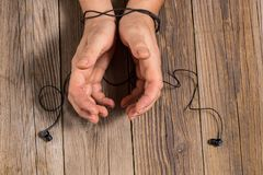 hands of man tied with phone headset, as the concept of man& x27;s dependence on music, technology Stock Photography