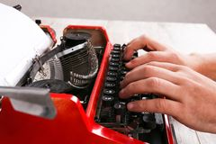 Hands of a man typing on a red typewriter maschine. The hands of a man typing on a red typewriter on a light wooden table. Close-up of hands and printing machine Royalty Free Stock Photography