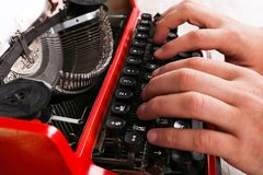 Hands of a man typing on a red typewriter maschine. The hands of a man typing on a red typewriter on a light wooden table. Close-up of hands and printing machine Royalty Free Stock Photo