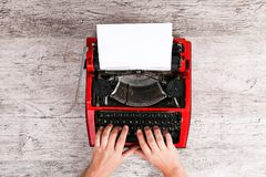 Hands of a man typing on a red typewriter maschine. The hands of a man typing on a red typewriter on a light wooden table. Close-up of hands and printing machine Royalty Free Stock Images