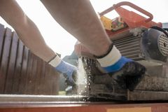 The hands of a man using an angle grinder. Close up on the hands of a man from behind using an angle grinder or circular saw outdoors to cut through a paving Stock Photo