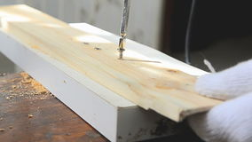 Hands of man using electric driller to spin the screw to the wood stock video footage
