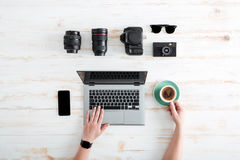 Hands of man using laptop and drinking coffee on table Stock Photos