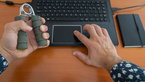 Hands of a man using laptop and exercising with spring-grip at office place, at the desk. Working and Exercising with hands at he same time. Body parts stock image