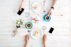 Hands of man and woman drinking coffee with cakes Royalty Free Stock Photos