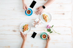 Hands of man and woman drinking coffee with croissants Stock Photography