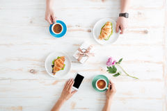 Hands of man and woman drinking coffee, using mobile phone Stock Image