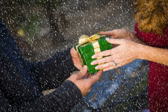 Hands of Man and Woman Exchanging Christmas Gift in Snow Stock Photo