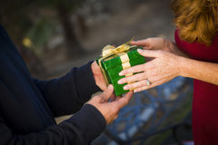 Hands of Man and Woman Exchanging Christmas Gift Stock Images