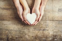 Hands of man and woman holding a heart together. Royalty Free Stock Image