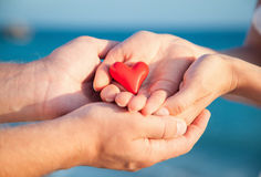 Hands of man and woman holding red heart protecting it together Royalty Free Stock Image