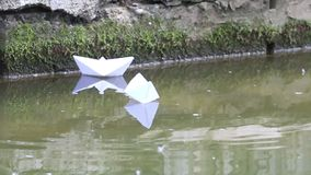 Hands of man and woman launching paper boats to water in park. At summer day stock video