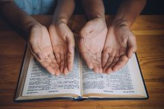 Hands of man and woman praying over the open bible stock photo