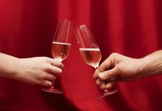 Hands Man and woman sitting at a table with glasses of champagne. Red background Stock Photo
