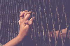 Hands of the man and woman on a steel lattice close up Royalty Free Stock Photo