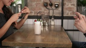 Hands of man and woman taking pictures of a glass with milk shake with cherry on the top and straw on a wooden table in stock video footage