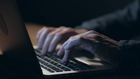 Hands of a man working on laptop at night. stock footage