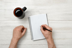 Hands of man writing with pencil in notebook and cup coffee standing on wooden table Royalty Free Stock Photography