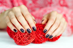 Hands with manicure touching decoration balls Royalty Free Stock Images