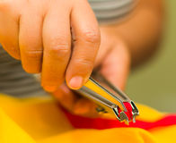 Hands manipulating special nipplers to make a zipper. Red color Stock Photos