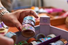 Hands manipulating Washi tape collection. In multiple designs Royalty Free Stock Image