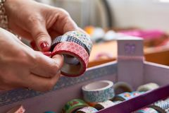Hands manipulating Washi tape collection. In multiple designs Stock Images