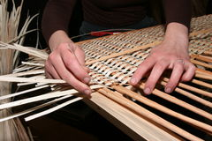 Hands manually mastering wicker fabric 5. Female hands manually mastering wicker fabric Royalty Free Stock Image