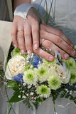 Hands married. Hands newlyweds on background of the wedding bouquet Stock Photography