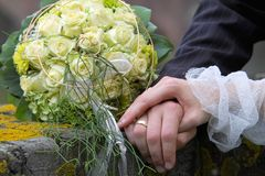 Hands on the married couple. Bouquet, rings and hands Stock Image