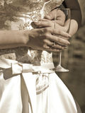Hands of married couple. Sepia toned shot of bridge holding glass. Husband arm round her waist stock photography