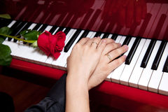 Hands of married couple on piano