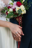 Hands of married couple with rings and wedding bouquet. Royalty Free Stock Photography