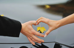 Hands of a married couple showing heart symbol Stock Image