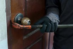 Hands of Masked thief with balaclava using crowbar to breaking into a house at night time. Crime concept. Hands of Masked thief with balaclava using crowbar to Royalty Free Stock Photo