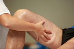 Hands massaging athlete's thigh after running Stock Photo