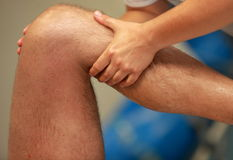 Hands massaging athlete's thigh after running Stock Images
