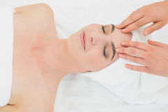 Hands massaging a beautiful woman's forehead at beauty spa Stock Photo