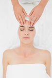Hands massaging a beautiful woman's forehead at beauty spa Stock Photography
